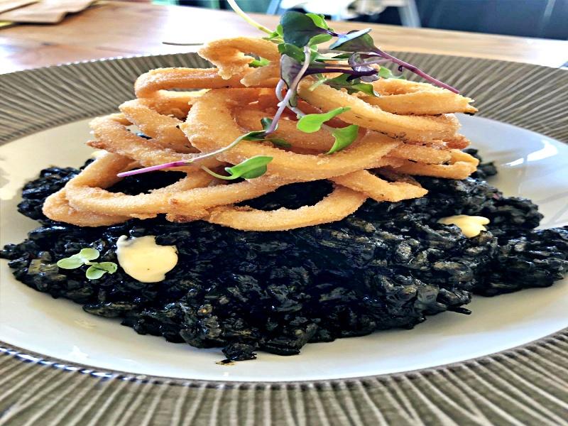Crujientes calamares sobre cama de arroz negro